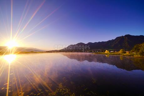 気嵐立つ水鏡の舌喰池と独鈷山と朝日の光芒の写真素材 [FYI02652153]