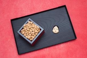 枡に入った煎り大豆とお多福のお面の写真素材 [FYI02652423]