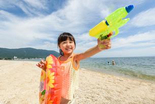 浮き輪と水鉄砲を持って遊ぶ女の子の写真素材 [FYI02652439]