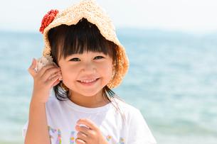 貝殻を耳に当てる女の子の写真素材 [FYI02652484]
