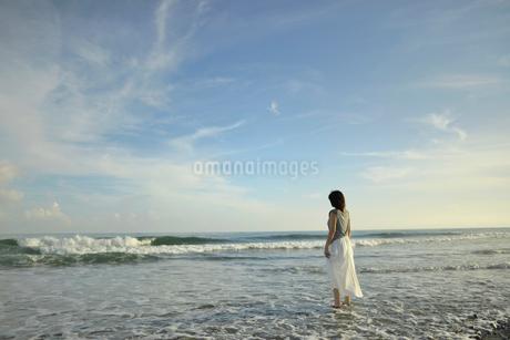 波打ち際に立つ妊婦の写真素材 [FYI02653973]