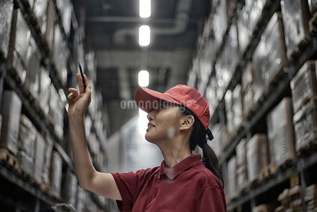 商品チェックしている物流センターの女性イメージの写真素材 [FYI02654331]