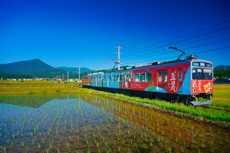 真田丸ラッピング電車と田園と夫神岳の写真素材 [FYI02654476]
