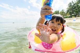 水鉄砲を持って浮き輪で泳ぐ女の子の写真素材 [FYI02654584]