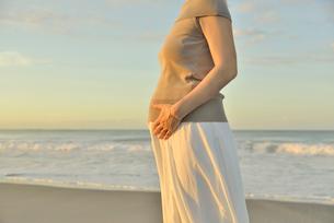 夜明けの海岸に立つ妊婦の写真素材 [FYI02654600]
