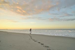 夜明けの海岸に立つ女性の写真素材 [FYI02654611]