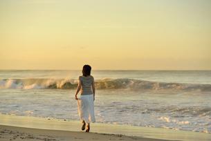 夜明けの海岸を歩く女性の写真素材 [FYI02654730]