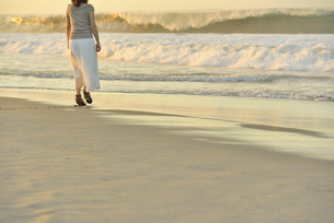 夜明けの海岸を歩く女性の写真素材 [FYI02654744]
