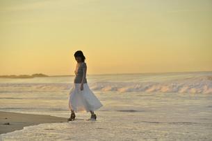 夜明けの海岸に立つ妊婦の写真素材 [FYI02654758]
