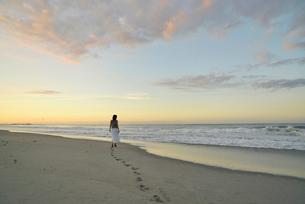 夜明けの海岸に立つ女性の写真素材 [FYI02655190]
