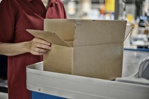 商品箱を包装している女性の写真素材 [FYI02655285]