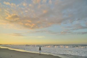 夜明けの海岸に立つ女性の写真素材 [FYI02655328]