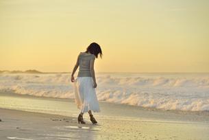 夜明けの海岸を歩く女性の写真素材 [FYI02655337]