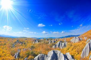 カルスト台地の石灰岩と雁飛山と花尾山などの山並みと太陽の光芒の写真素材 [FYI02655385]