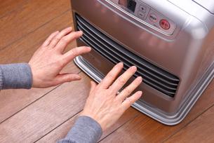 石油ファンヒーターで手を温めるの写真素材 [FYI02655448]