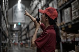 無線機を持って倉庫の中で働いている女性イメージの写真素材 [FYI02655563]