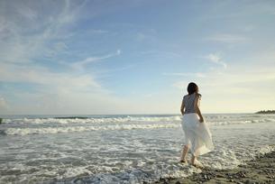 波打ち際に立つ妊婦の写真素材 [FYI02655595]