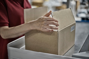 商品ボックスを包装している女性イメージの写真素材 [FYI02655613]