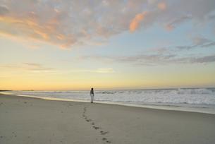 夜明けの海岸に立つ女性の写真素材 [FYI02655655]