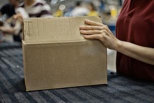 商品箱を包装している女性の写真素材 [FYI02656040]