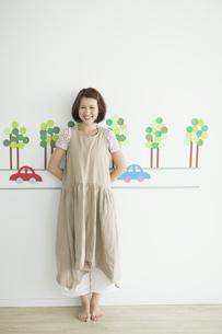 壁のイラストの前に立つ若い女性の写真素材 [FYI02656103]
