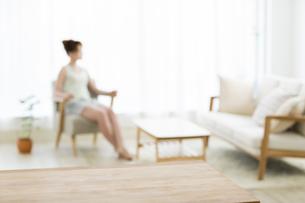 テーブルとソファーに座る女性の写真素材 [FYI02656109]