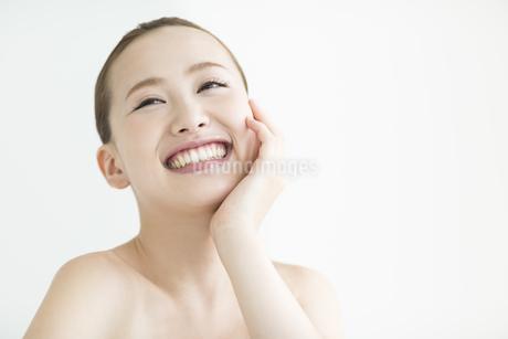 頬に手をあてる女性のスキンケアイメージの写真素材 [FYI02656110]