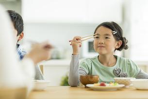 箸の持ち方を練習する女の子の写真素材 [FYI02656156]