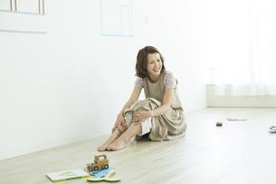 床に座る笑顔の女性の写真素材 [FYI02656210]