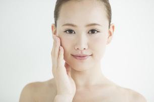 頬に手をあてる女性のスキンケアイメージの写真素材 [FYI02656482]
