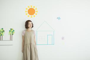 壁のイラストの前に立つ若い女性の写真素材 [FYI02656560]