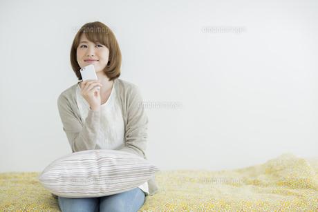 携帯電話を顎にあてて考え事をする女性の写真素材 [FYI02656565]