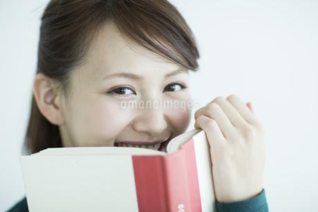 本を口元にあてる女性の写真素材 [FYI02656601]