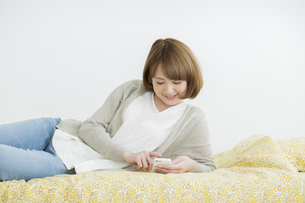 ベッドの上で携帯電話を操作する女性の写真素材 [FYI02656603]