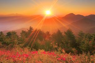 浅間山から昇る朝日と冠着山などの山並みと紅葉の樹林の写真素材 [FYI02656710]