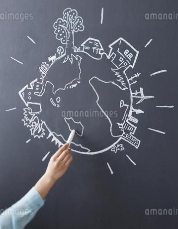 黒板に地球の絵を描く女性のイラスト素材 [FYI02656853]