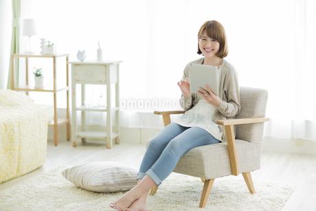 タブレットPCを持って笑顔の女性の写真素材 [FYI02657114]