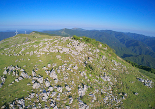 姫鶴牧場の石灰岩群と妙見森などの山並みと風力発電の風車の写真素材 [FYI02657288]