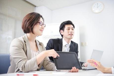 会議にて提案をするスーツの女性と部下の写真素材 [FYI02657664]