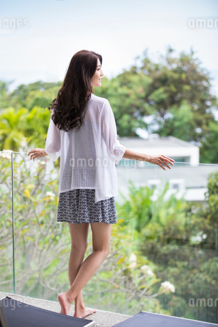 Happy young Chinese woman relaxing on balconyの写真素材 [FYI02658044]