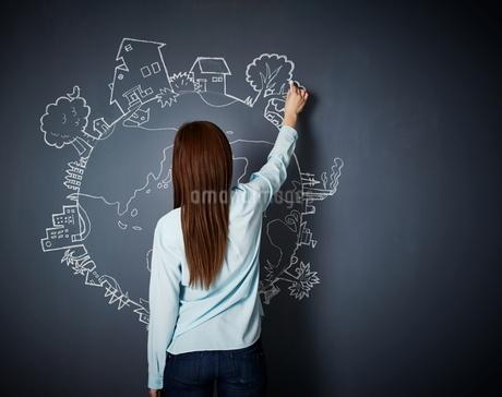 黒板に地球の絵を描く女性のイラスト素材 [FYI02658376]