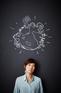 黒板に描かれた地球の絵の下で悲しむ女性のイラスト素材 [FYI02658832]