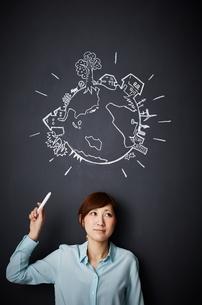 黒板に描かれた地球の絵を指す女性のイラスト素材 [FYI02658941]