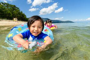 浮き輪を使って泳ぐ男の子と女の子の写真素材 [FYI02659143]