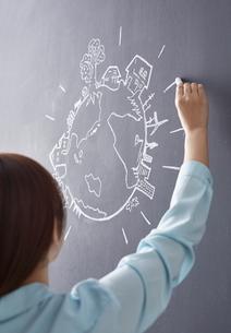 黒板に地球の絵を描く女性のイラスト素材 [FYI02659247]