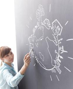 黒板に地球の絵を描く女性のイラスト素材 [FYI02659265]