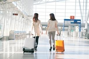キャリーバッグをひいて歩く2人の女性の後ろ姿の写真素材 [FYI02659590]