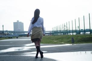 水たまりを歩く女学生の後ろ姿の写真素材 [FYI02660923]