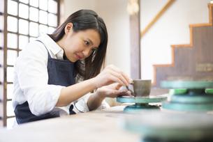 陶芸教室でろくろを回している女性の写真素材 [FYI02660989]