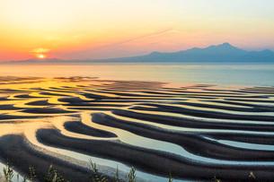 御輿来海岸の砂紋と海と夕日と雲仙岳の写真素材 [FYI02661139]